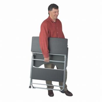 A black compact computer desk is folded up and carried by a man.