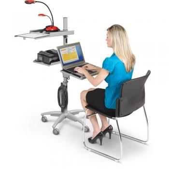 A woman is seated at a AV projector cart.