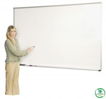A woman stands in front of the magnetic porcelain steel dry erase classroom white board.