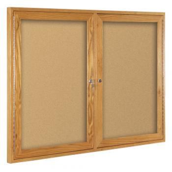 A double two door enclosed cork board is shown in oak.