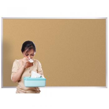 A woman is shown standing in front of a standard cork board with a box of tissues.