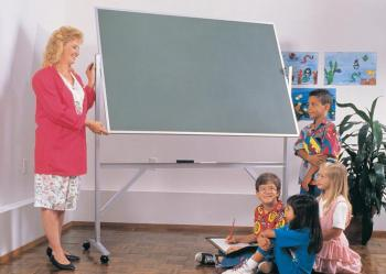 A teacher in s classroom standing in front of a green chalkboard easel.