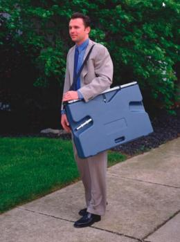 A man is carrying a portable presentation whiteboard.