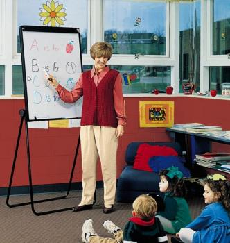 A teacher is in a classroom, directing students to a portable marker board.
