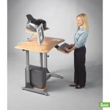 A woman is standing and using a sit down or stand up adjustable computer workstation.