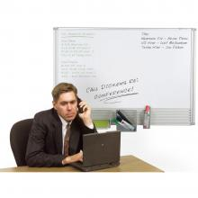 A man sits at an office desk in front of a small white board.