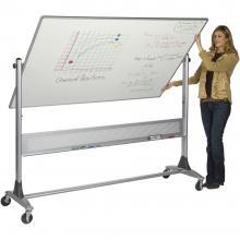 A teacher stands beside a standing dry erase board.