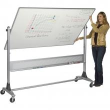 A teacher stands beside a large double sided dry erase board.