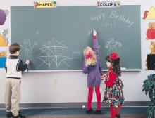 Students drawing with chalk on a green slate chalkboard in a classroom.