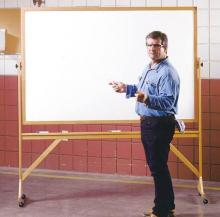 A rolling whiteboard in a classroom.