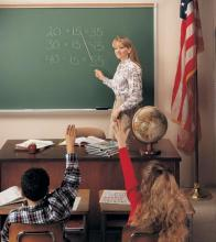 A teacher is shown instructing a class in front of a large  green chalkboard.