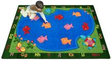 A student sits on a rectangular shaped kids floor rug with fish.