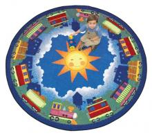 "A boy sits on a circle shaped ""In Training"" train nursery rug."