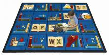 A student sitting on a rectangle shaped alphabet daycare rug.