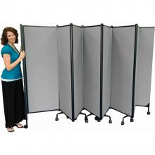 A lady stand beside folding room dividers.