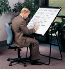 A man in an office is preparing a presentation on a portable marker board.